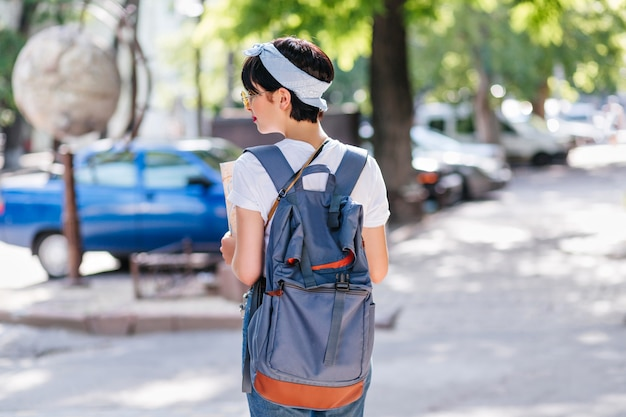 Outdoor portrait from back of graceful female traveler with short black hair spending time outdoor walking by cars