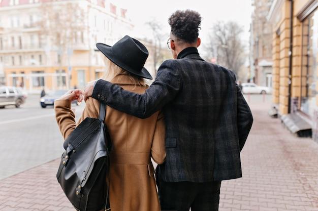 秋の日に路上で時間を過ごす国際的なカップルの後ろからの屋外の肖像画。金髪の女性を優しく抱きしめるダークグレーのジャケットを着たスタイリッシュなアフリカ人男性。