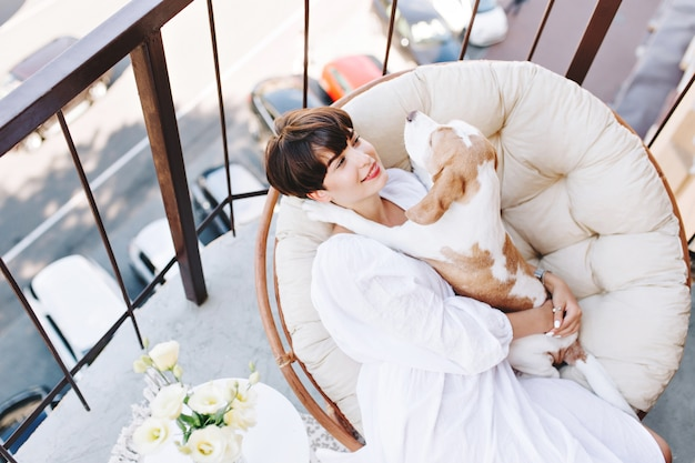 Outdoor portrait from above of playful beagle lies in chair next to smiling girl