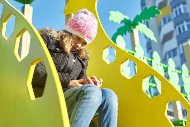 Открытый портрет девочка 8, 9 лет со смартфоном, девочка весеннего сезона в куртке.