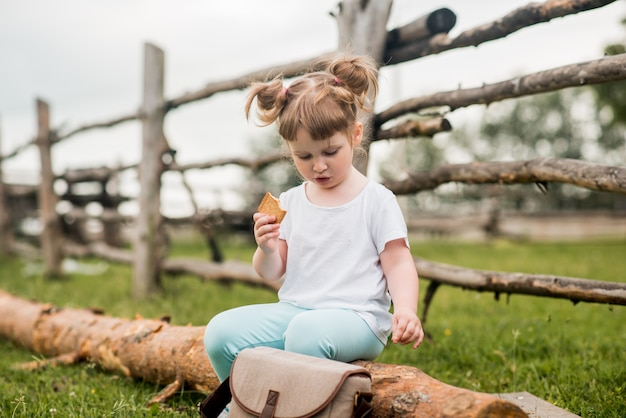 Outdoor portrait of a girl sitting on the grass near the fence.summer in the village. beautiful baby girl on a wooden bench.ecology and happy childhood.