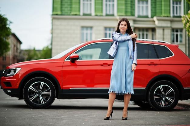 Outdoor portrait of gorgeous woman posing near orange suv car