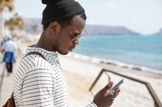 Outdoor portrait of handsome african blogger in shades traveling in european resort using smartphone for sharing posts and uploading pictures, looking serious and concentrated standing on sea beach