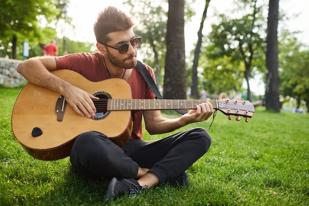 Outdoor portrait of handsome hipster guy sitting on grass in park and playing guitar