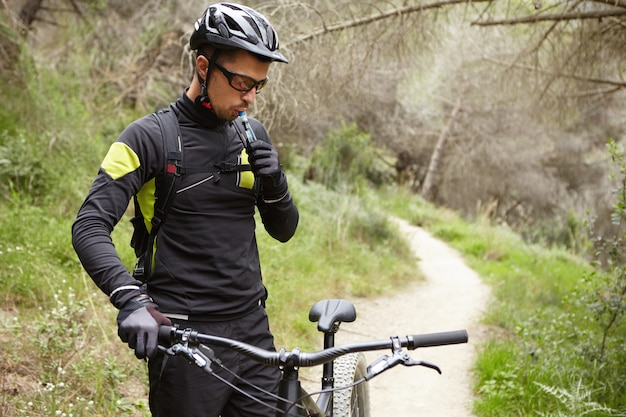 Outdoor portrait of handsome professional rider in cycling clothing holding handlebar of black motor-powered bike, drinking water out of plastic tube during small break while riding in woods