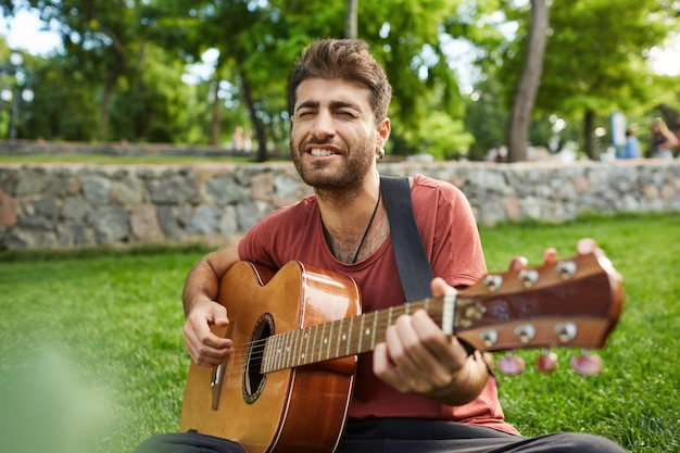 Outdoor portrait of handsome romantic guy sitting on grass in park and playing guitar