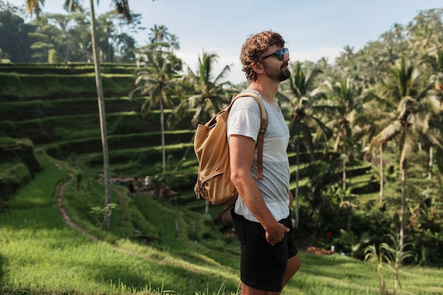 Outdoor portrait of handsome travel man with back pack walking on rise terrace in bali.