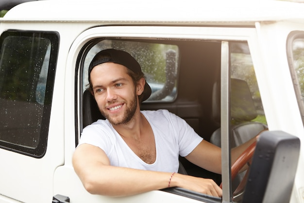 Outdoor portrait of handsome young bearded male in baseball cap sticking out his head out of open window of his white car smiling