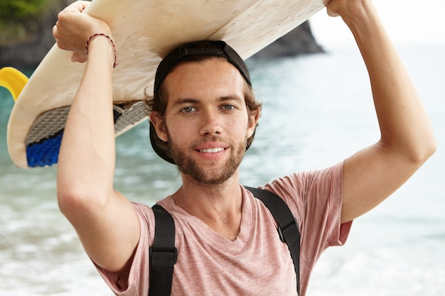 Outdoor portrait of handsome young surfer wearing snapback backwards posing against blue sea, holding his white bodyboard over his head, smiling happily