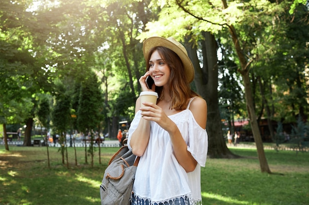 Outdoor portrait of happy beautiful young woman wears stylish hat, white blouse and striped backpack, feels relaxed, talking on mobile phone and drinking takeaway coffee in park in summer