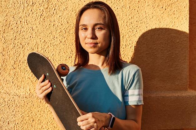Ritratto all'aperto di felice donna dai capelli scuri che indossa una maglietta in posa isolata sul muro giallo, guardando la macchina fotografica d'arte, tenendo lo skateboard in mano, estate, tramonto.