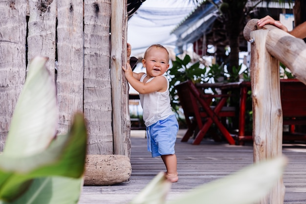 Outdoor portrait of happy nine months old kid in blue short and white shirt stands by wooden wall and smile