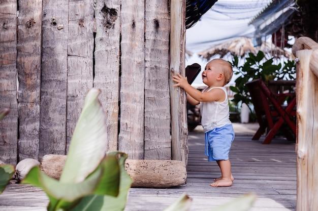 Ritratto all'aperto di bambino di nove mesi felice in camicia bianca e corta blu si leva in piedi dalla parete di legno e dal sorriso