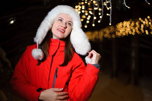 Outdoor portrait of happy smiling girl wearing white fur hat. model posing in the night park with christmas lights. winter holidays concept.