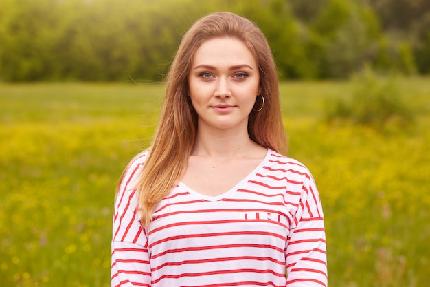 Outdoor portrait of happy smiling girl with long straight hair in white shirt with red stripes posing in summer meadow, has calm and pleasant facial expressions, being photographed by friend.