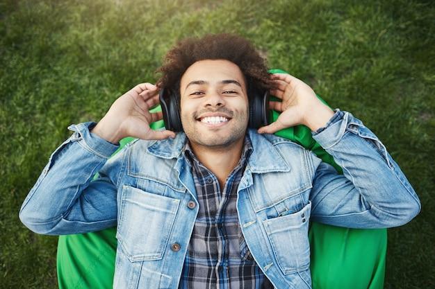 Ritratto all'aperto di felice ottimista maschio dalla carnagione scura con setole e taglio di capelli afro sdraiato sulla sedia a sacco o sull'erba, sorridendo ampiamente mentre ascolta la musica tramite le cuffie e tenendoli con le mani