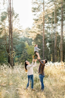 Outdoor portrait of happy young parents, having fun and lifting up their little cute baby son, during walk in autumn forest at sunny day