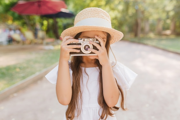 Outdoor portrait of inspired little girl spending time in park and making photo of nature views. child in hat with long brown hair holding camera standing on the road