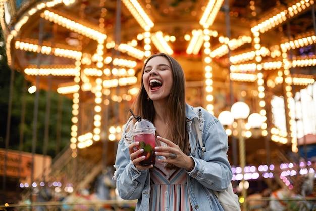 Ritratto all'aperto di gioiosa giovane femmina bella mora in abiti casual in posa sul parco di divertimenti con gli occhi chiusi e un ampio sorriso, che tiene la tazza di limonata nelle mani