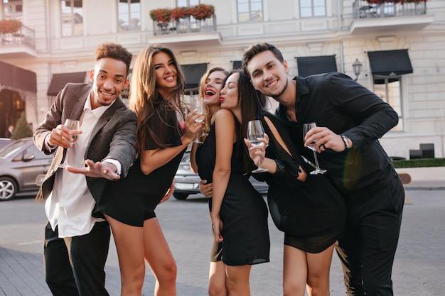 Ritratto all'aperto di ridere studenti che celebrano la laurea in prima serata