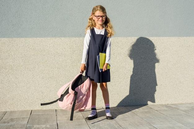 Outdoor portrait little girl with school backpack