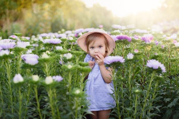 야외 초상화. 아름 다운 정원에서 꽃과 작은 유아 사랑스러운 소녀. 자연 속에서 야외에서 아이
