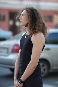 Outdoor portrait of modern young man walk street. man with long curly hair.