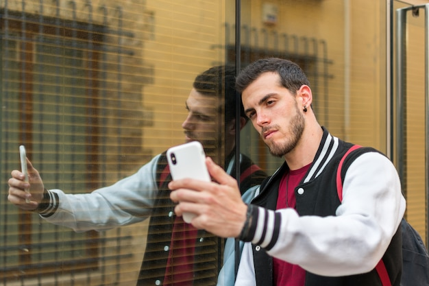 Outdoor portrait of modern young man with mobile phone