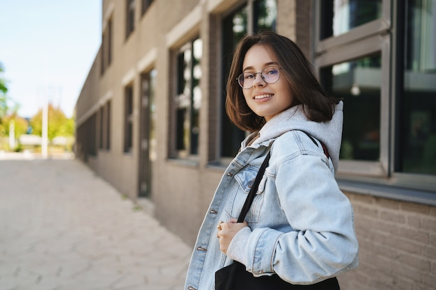 Outdoor portrait of modern young queer girl, female student in glasses and denim jacket, going home after classes, turn back to smile at camera, waiting for friend walking on sunny street.