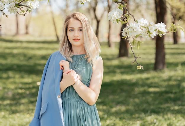 Открытый портрет красивой блондинки в зеленом платье и синем пальто среди цветущих яблонь