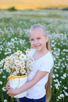 カモミールフィールドの表面に対して6〜7歳のかわいい女の子の屋外の肖像画