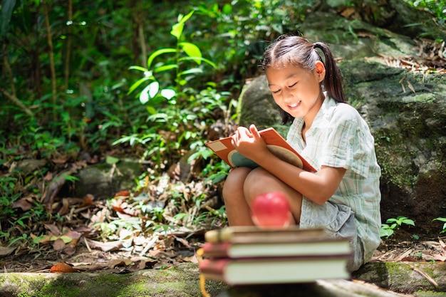 かわいい女の子の本を読んでいる屋外の肖像画