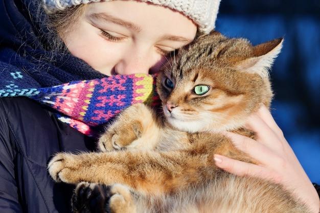 彼女の赤い猫を保持している幸せな十代の少女の屋外の肖像画。冬のシーン。