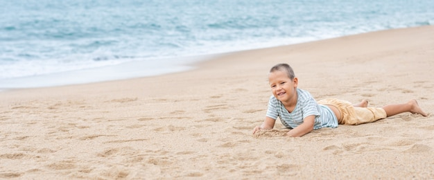 모래 해변에 누워 작은 귀여운 소년의 야외 초상화. 파노라마