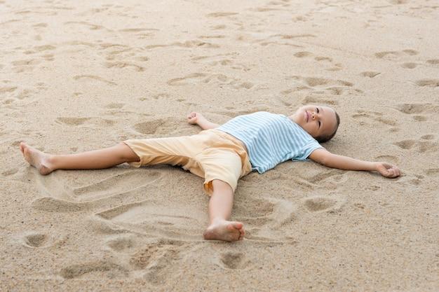 모래 해변에 누워 작은 귀여운 소년의 야외 초상화.