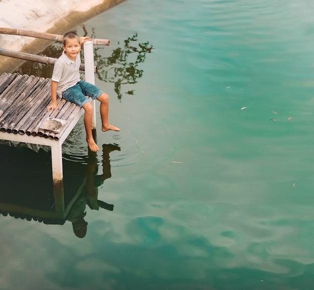 호수의 부두에 앉아 작은 귀여운 소년의 야외 초상화