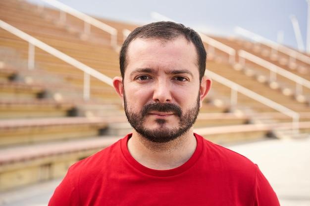 Открытый портрет человека, смотрящего в камеру на фоне стадиона