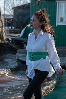緑のベルトと白いシャツで湖でポーズをとる中年の女性の屋外の肖像画