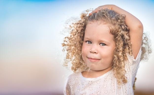 웃는 어린 소녀의 야외 초상화입니다. 긍정적 인 감정 개념.