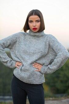 通りでポーズをとってニットセーターを着ているスタイリッシュな日焼けした女性の屋外の肖像画