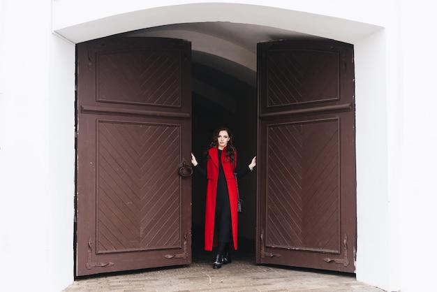 黒の服と長い赤いベストで旧市街の通りにスタイリッシュな若い女の子の屋外の肖像画。モデルがヨーロッパの都市の通りでポーズをとる