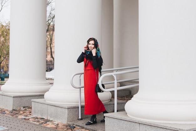 黒い服と長い赤いベストと彼女の頭の上のロシアのスカーフで旧市街の通りにスタイリッシュな若い女の子の屋外の肖像画。モデルがヨーロッパの都市の通りでポーズをとる