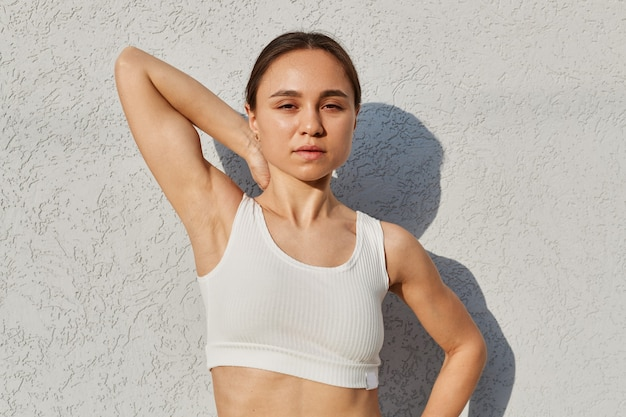 흰 벽 근처에서 팔을 들고 포즈를 취하고, 카메라를 보고, 운동하는 동안 사진을 찍고, 건강한 생활 방식을 취하는 젊은 운동 소녀의 야외 초상화.