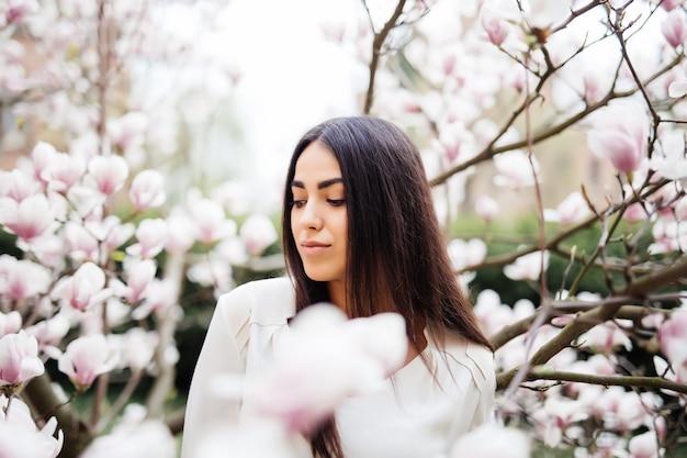 꽃과 목련 나무 근처 젊은 아름 다운 여자의 야외 초상화. 세련 된 옷을 입고 소녀입니다.
