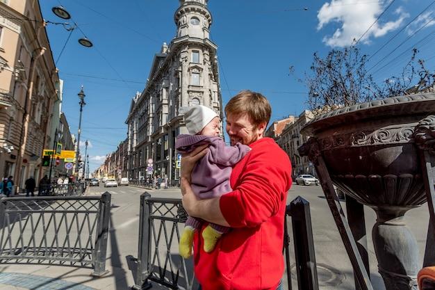 彼の小さな幼児を元気づけようとしている若い父親の屋外の肖像画