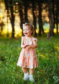 夏の日の愛らしい笑顔の少女の屋外のポートレート