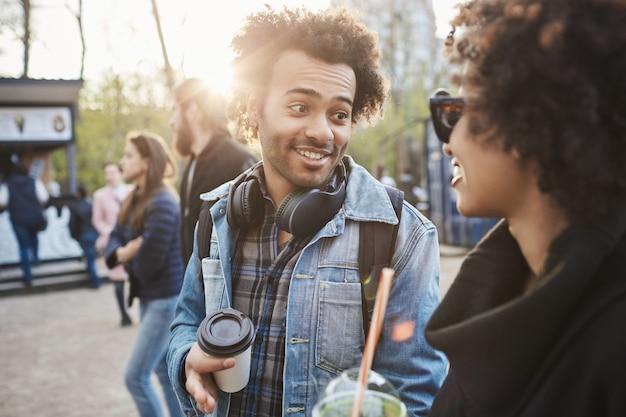 トレンディな服を着て話したり、コーヒーを飲みながら公園を歩いているアフリカ系アメリカ人の友人の屋外のポートレート。