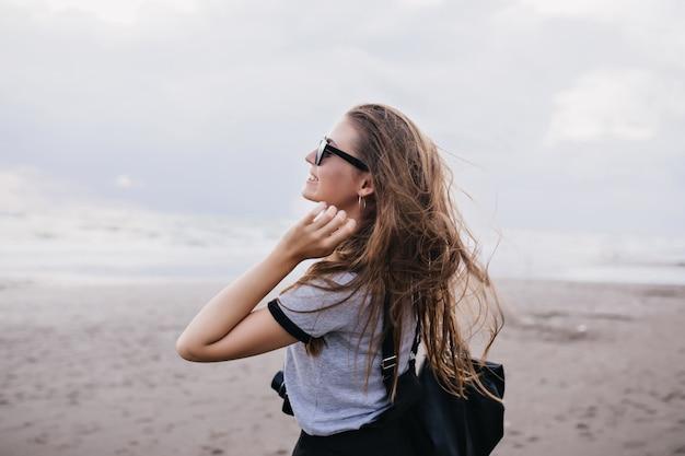 Открытый портрет удивительной девушки с длинными темными волосами, выражающими счастье во время прогулки по пляжу. вдохновленная женская модель в серой футболке проводит время у моря в пасмурный день.