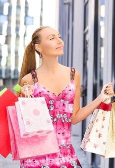 ショッピングバッグを持つ魅力的な女性の屋外の肖像画