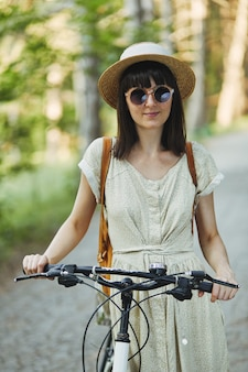 Внешний портрет привлекательного молодого брюнет в шляпе на велосипеде.